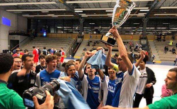 Photo d'une équipe les bras levés avec une coupe après la victoire d'un tournoi de futsal