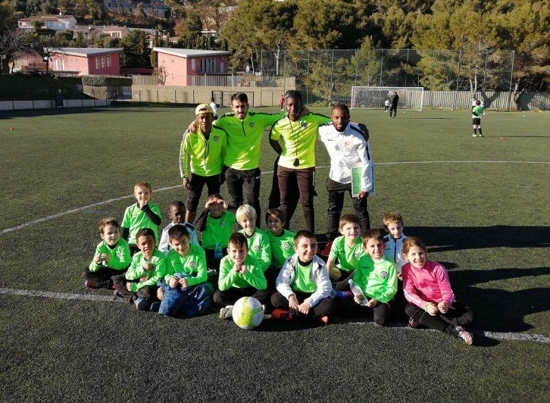 Photo de groupe d'une équipe du FC Beausoleil sur le terrain avec des encadrants
