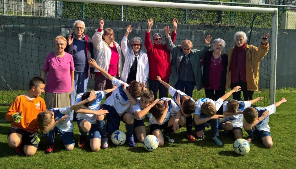 """Photo de groupe de l'école de """"foot social"""" sur un terrain"""