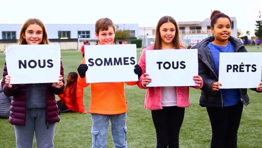 """4 enfants qui tiennent des pancartes avec écrit : """"Nous Sommes Tous Prêt"""""""