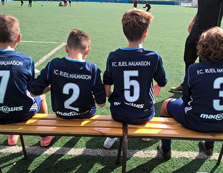 Photo de 4 enfants assis sur un banc de dos et portant le maillot deu club FC Rueil Malmaison