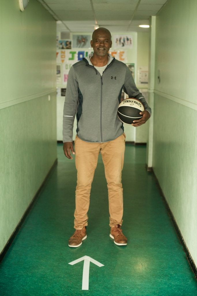 Abdoulaye Ndiaye pose dans un couloir avec un ballon de basket