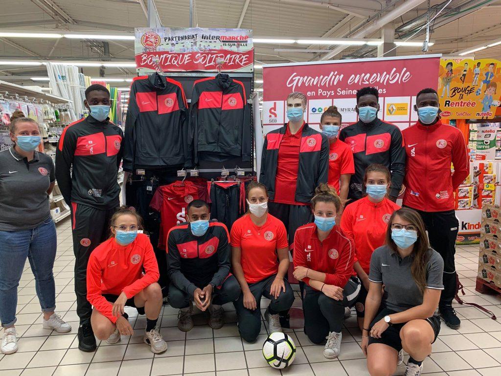 Photo de groupe dans un supermarché avec les maillots du club en rayon