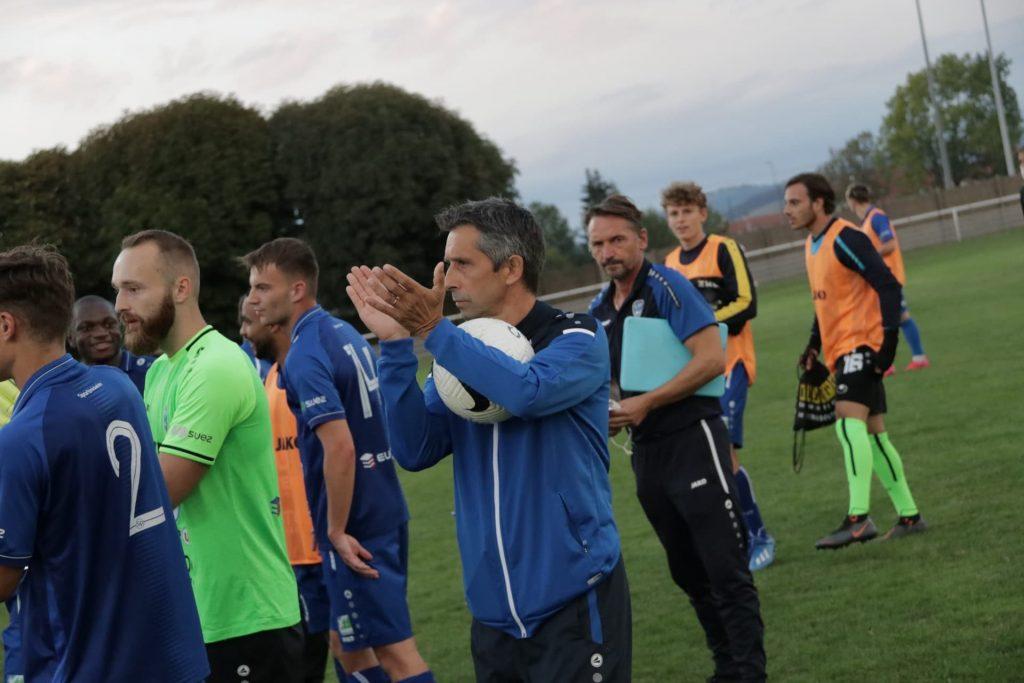Jean-Luc Courtet sur le terrain entouré par d'autres joueurs