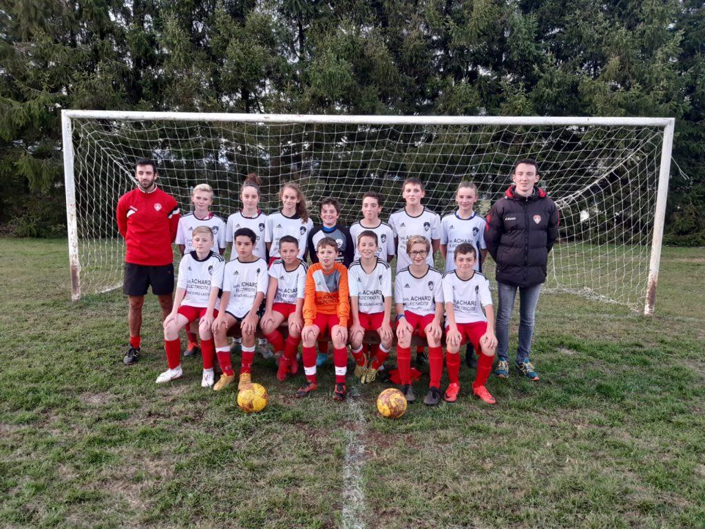Photo de groupe, d'une équipe sur le terrain devant des cages de football