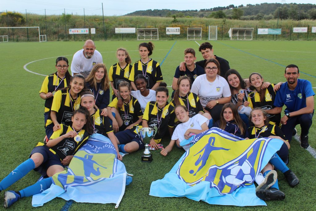 Photo de groupe d'une équipe féminine sur le terrain avec les drapeau à l'effigie du club