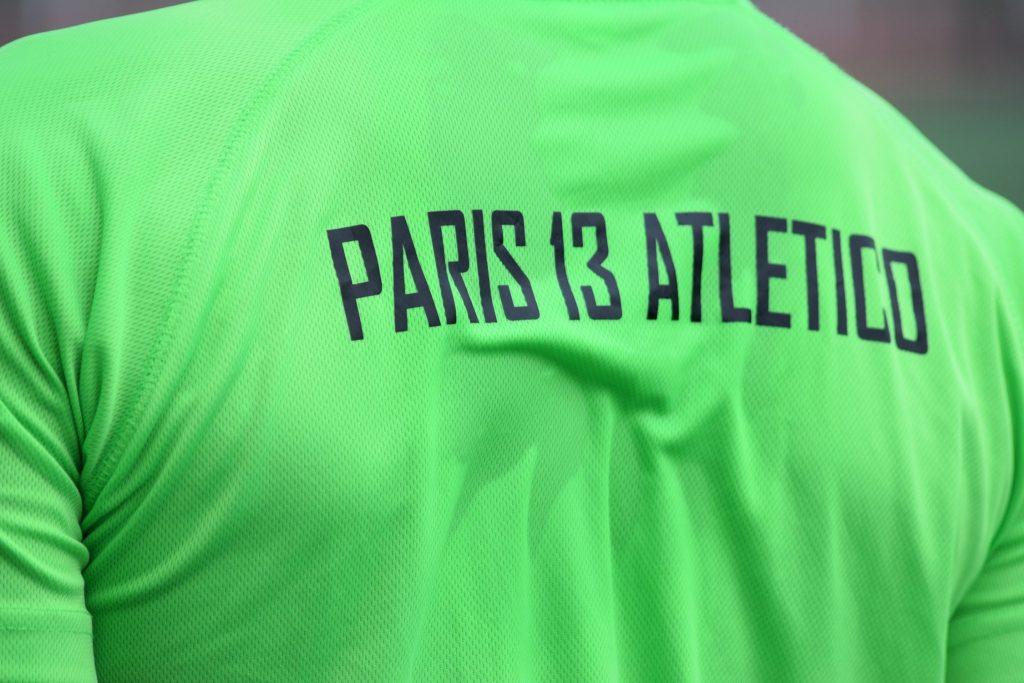 """photo d'un maillot vert de dos avec l'inscription """"Paris 13 Atletico"""""""
