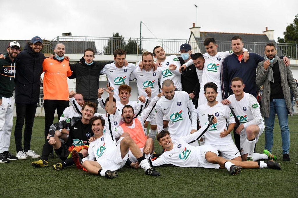 Photo de groupe en tenue de foot  sur le terrain