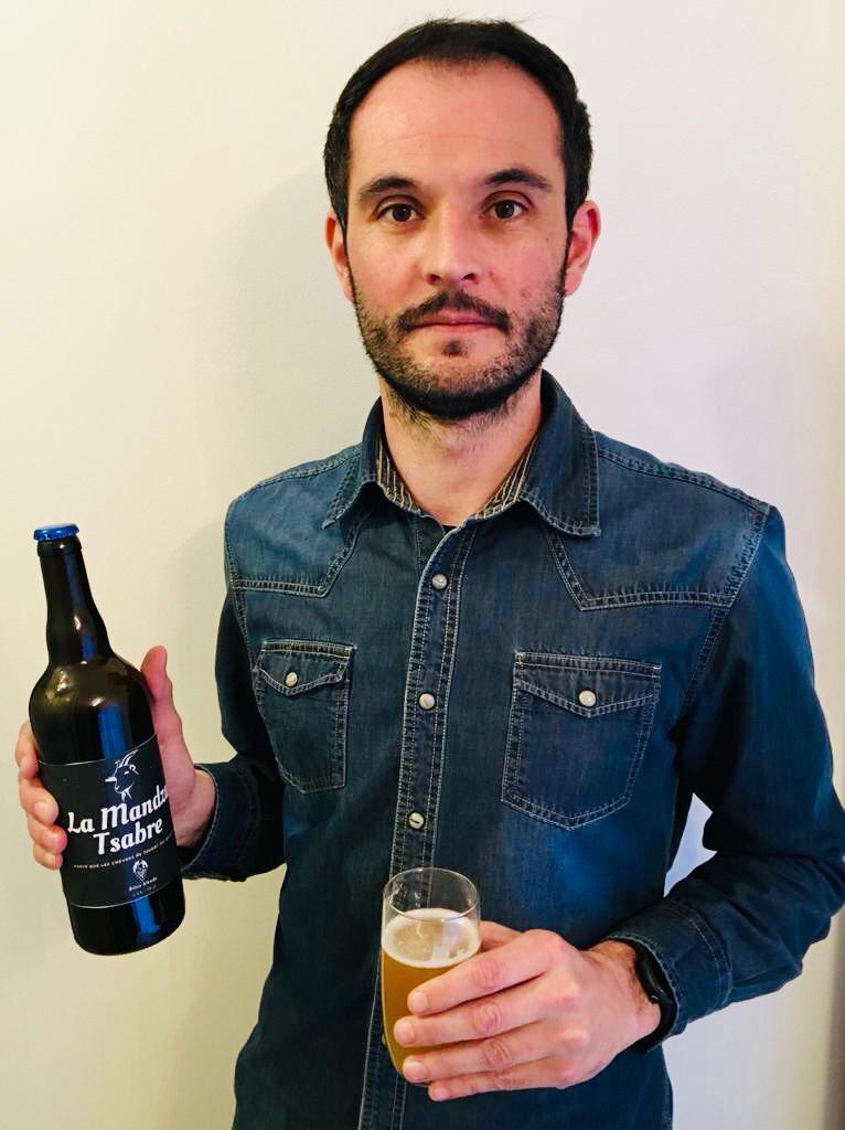 Homme tenant une bouteille et un verre